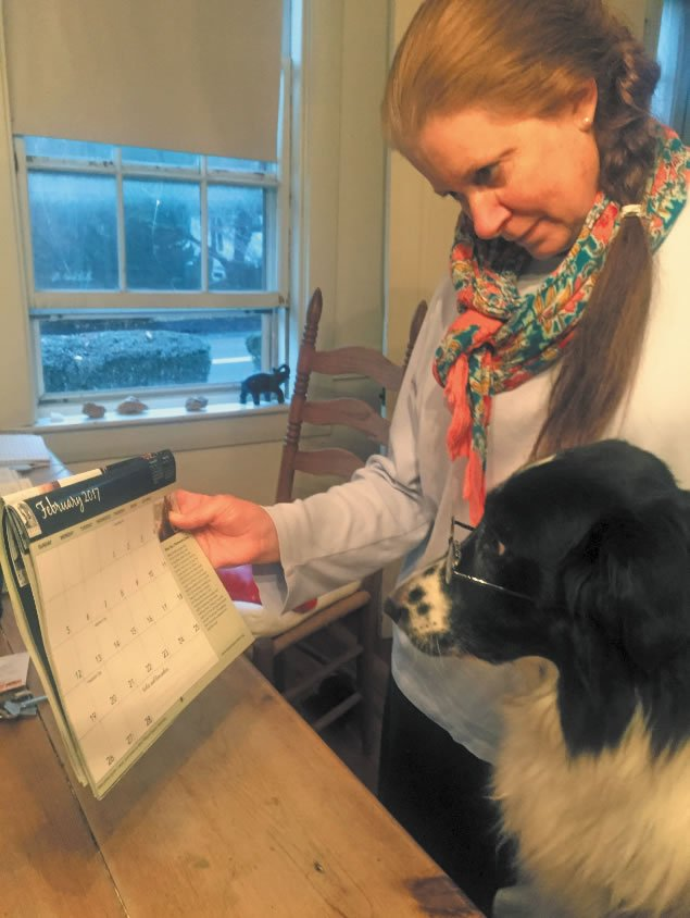 "Border collie Franklin checks the calendar with his ""mom"""
